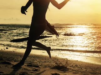 Silhouette of woman running along shore of ocean