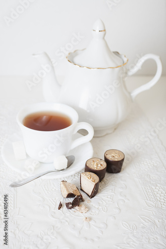 cup of tea, teapot and candies