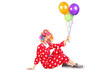 Clown holding balloons seated on the floor