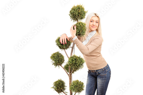 Blond girl hugging a plant isoalted on white background