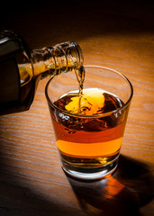 brandy or whiskey pouring into glass