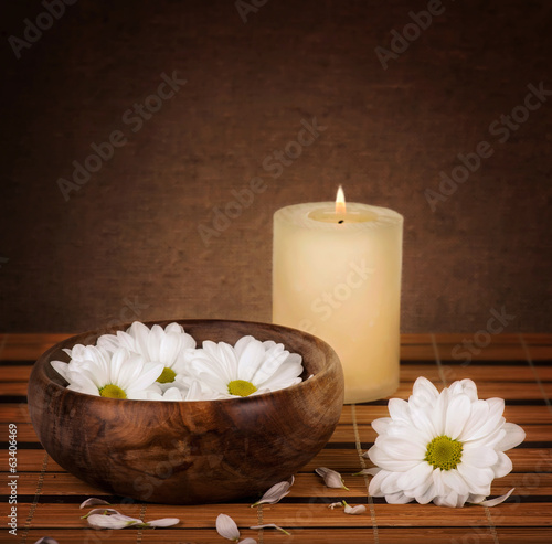 Spa decoration with candle and daisies floating in water