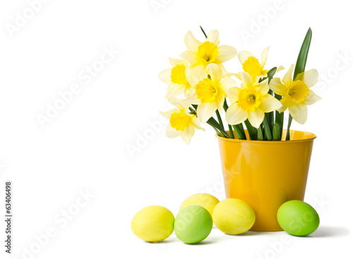 Easter eggs and daffodils in a yellow flowerpot