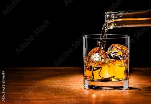 Foto op Plexiglas Alcohol Pouring whiskey drink into glass