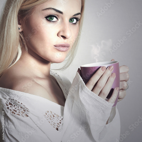 Beautiful blond woman drinking a Tea.Vapor Cup of Coffee.Hot