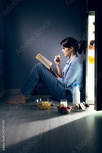 Sleepless woman reading in the kitchen - 63407610