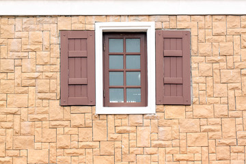 Windows of homes with brick wall surround.