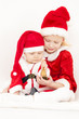 two little girls as Santa Clauses with a bell