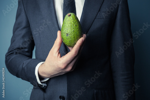 Businesman holding avocado