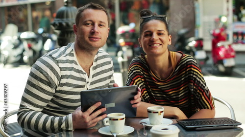 couple drinking coffee and using cellphones by the table outside