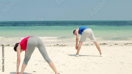 Young couple exercising on beautiful beach
