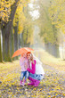 mother and her daughter with umbrella in autumnal alley