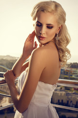 beautiful bride with blond hair posing at the balcony