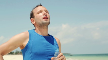 Male jogger drinking water after workout on the beach