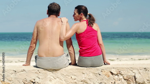 Sporty couple relaxing after workout by the sea
