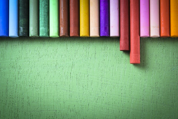 Crayons lined up in rainbow isolated on green background