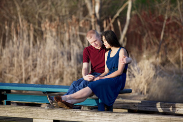 Young interracial couple enjoying time together on wooden pier o