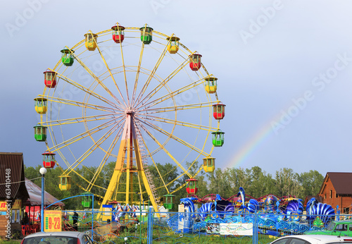 Ferris wheel and rainbow at an amusement park. Village Aya. Alta