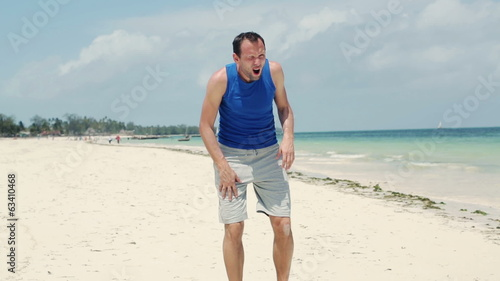 Tired jogger having a break during jogging on the beach