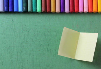 Crayons lined up in rainbow isolated on green background, note p