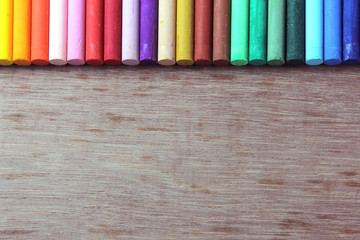 Crayons lined up in rainbow isolated on wood background