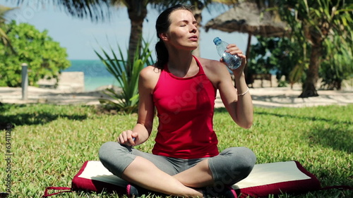 Young woman drinking water, resting after workout in garden