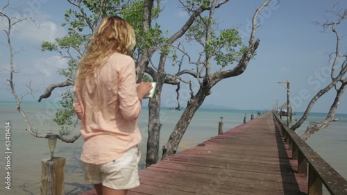 Young woman using digital tablet in tropical settings
