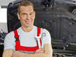 canvas print picture - Master mechanic in a garage in front of a car