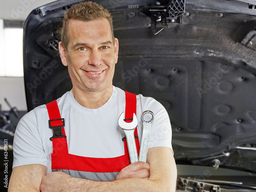canvas print picture Master mechanic in a garage in front of a car