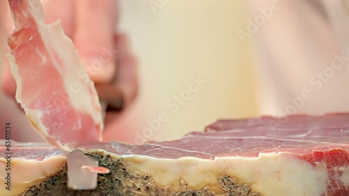 hands cutting slice dried ham
