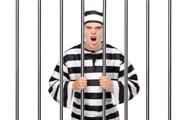 Angry prisoner standing behind bars