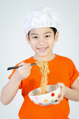 Asian cute child eating ramen noodles in ceramic bowl .