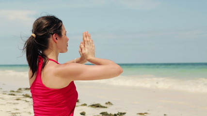 Young beautiful woman meditating on the beach