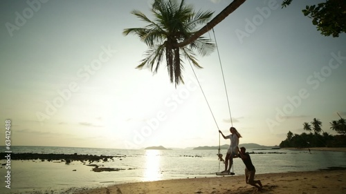 Young couple using playing on a swing by the beach