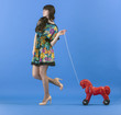 Beautiful young woman walking pulls a toy horse on a rope.