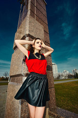 stylish brunette model in red colorful cloth in the street