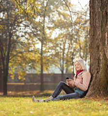 Girl sitting by a tree in park and writing sms