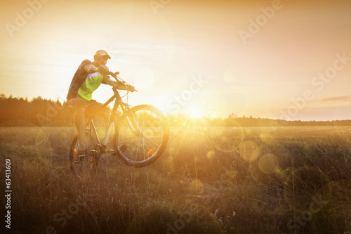 Young man riding a bike at sunset