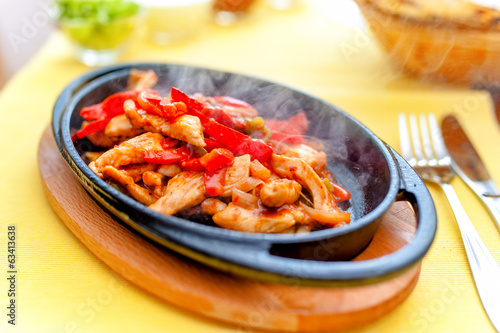 chicken fajita smoking hot on iron plate and vegetables