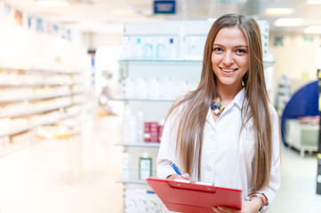 portrait of smiling young blonde pharmacist at drug store