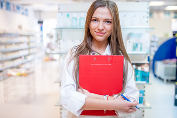 Female health care worker smiling in pharmacy
