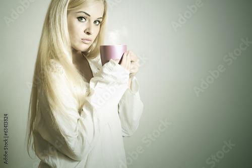 Beautiful woman drinking Coffee.Vapor Cup of tea after sleep