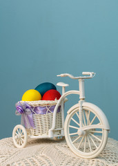 The bike with colored eggs in the basket on a blue background