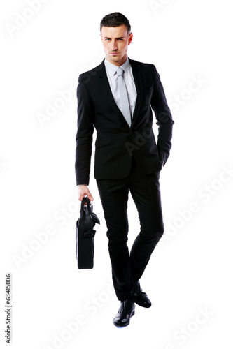 Confident businessman walking with laptop bag
