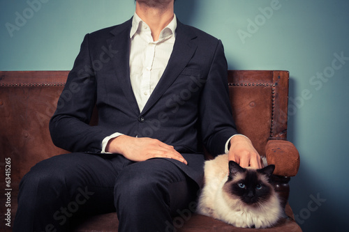 Young man and cat relaxing on sofa