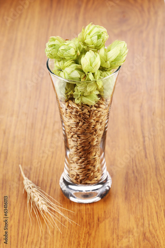 Glass with hop and wheat.