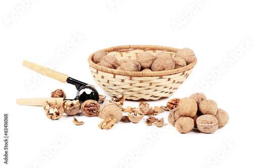 Walnuts in basket and nutcracker.