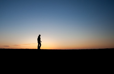 silhouetted man in sunset