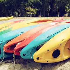 Bright kayaks on the beach. Colourful canoe. Filtered image