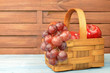 Wooden basket with red apples and bunch of grapes
